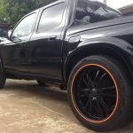 black pickup truck with orange RimBlades rim protectors